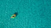 Aerial View Of Slim Woman Swimming On The Swim Ring  Donut In The Transparent Turquoise Sea In Seych poster