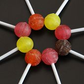 Sweet Multicolored Caramel On A Stick. Sweets Laid Out On The Table. Sweet Life On A Dark And White  poster