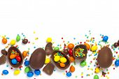 Broken And Whole Chocolate Easter Eggs, Multicolored Sweets On White Background. Concept Of Celebrat poster