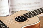 Ukulele Chords. Close-up Photo Of Ukulele Guitar And Music Notes Against Of Wooden Background. Music poster