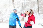 Snowball fight. Winter couple having fun playing in snow outdoors. Young joyful happy multi-racial c