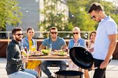 leisure and people concept - happy man grilling on bbq and friends at rooftop party poster