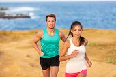 Fit run people couple jogging for fitness running on beach landscape nature outdoors. Woman and man  poster