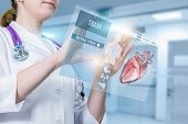 A Doctor Is Standing And Operating With Patient Digital Medical Card Or Digital Heart Treatment Stru poster