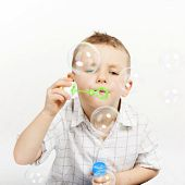 Pretty, cute boy blowing soap bubbles