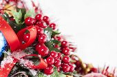 stock photo of winterberry  - Christmas border with red Holly berries and ribbon covered by snow - JPG