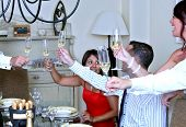 Smartly Dressed Guests At A Dinner Party Toasting With Champagne