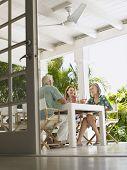 Vista de ángulo bajo de tres personas de mediana edad, sentado en la mesa de la terraza