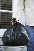 Closeup midsection of a man putting garbage bag into trash can