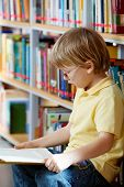 stock photo of clever  - Portrait of clever boy reading book in library - JPG