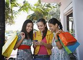 Happy teenage girls with shopping bags text messaging outdoors