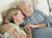 Closeup elevated view of a happy middle aged couple embracing in bed