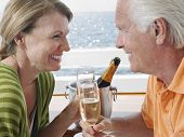 Side view of happy middle aged couple drinking champagne on yacht
