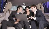 Three businesspeople looking at laptop in limousine