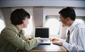 Businessman and businesswoman using laptop on private airplane