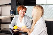 Happy adult woman with daughter on kitchen. Family at home talking and drinking tea