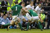 TWICKENHAM LONDON, 27/02/2010. Mark Cueto  is tackled by  Cian Healy and  David Wallace  during the