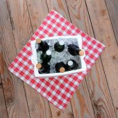 Overhead shot of a styrofoam ice chest full of beer bottles on a red and white checked table cloth o