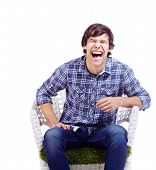 picture of laugh out loud  - Young man in checkered shirt and blue jeans sitting in white chair and laughing - JPG