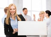 business and advertising concept - smiling businesswoman with white blank board