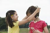 Cute little girl giving friend daisy chain in meadow