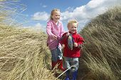 Full length of brother and sister standing among long grass