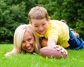 Child tackling mom while playing football together outdoors
