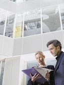 Low angle view of two business people looking at folder in office atrium