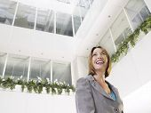 Smiling businesswoman standing in atrium of office building low angle view