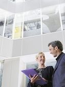 Low angle view of two smiling business people with a folder in office atrium