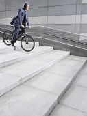Side view of a businessman in crash helmet riding bicycle down steps
