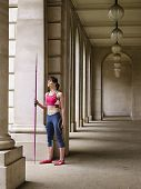 Full length of a female athlete with javelin in portico