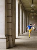 Full length of a soccer player kicking ball in portico