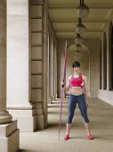 Full length portrait of a female athlete with javelin in portico