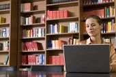 Beautiful and serious young woman using laptop in the library