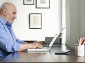 Side view of a mature man sitting at desk and using laptop