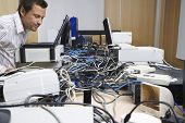 Side view of a male office worker looking at wire mess connecting computers and printers in office