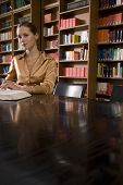 stock photo of shelving unit  - Portrait of a beautiful young woman sitting with book at desk in library - JPG