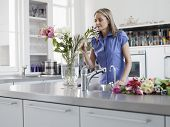 Middle aged woman smelling flowers in vase in kitchen
