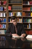foto of shelving unit  - Serious young man studying at desk in library - JPG