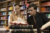 stock photo of shelving unit  - Young man and woman studying at desk in the library - JPG