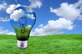 stock photo of light-bulb  - Global Concept of Green Energy Solutions With Light bulb and Planet on Bright Landscape - JPG