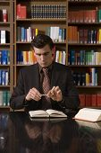 pic of shelving unit  - Serious young man in suit holding pen over book at desk in the library - JPG