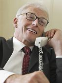 Closeup of a smiling middle aged businessman using landline phone