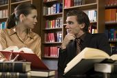 stock photo of shelving unit  - Smiling young man and woman with books at desk in the library - JPG