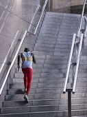 Rear view of a male athlete running up staircase outside building