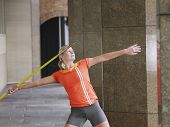 Young female athlete throwing javelin in portico