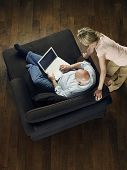 Top view of a woman watching mature bald man use laptop on sofa at home