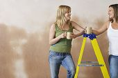 Two young women leaning on step ladder with mugs against brown wall