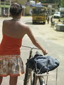 Rear view of a young woman on street walking with bicycle